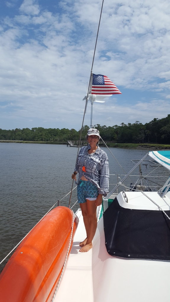 Sue standing on the deck of the yacht, anchored in the river